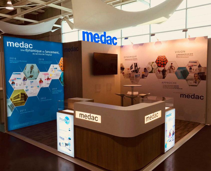 Conception et aménagement d'espace stand pour Medac France sur le congrès Hopipharm 2018. Solutions stands menuiserie et rétro éclairage. Plancher technique