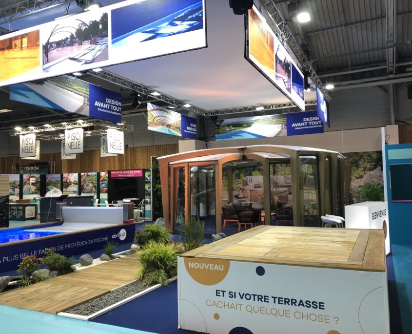 Scénographie - Agencement et conception stand de 500 m2 pour Abrisud. Location de mobilier / Décoration florale et habillage des sols - Habillage spécifiques pour les piscines et abri de piscine.